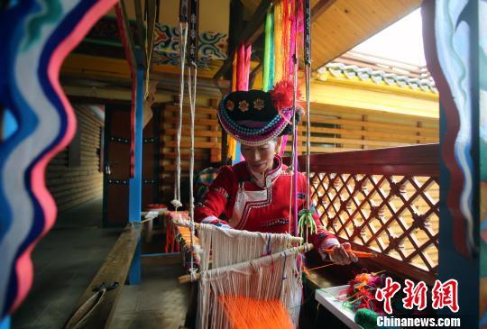 喇娜姆在编织花腰带。王磊 摄